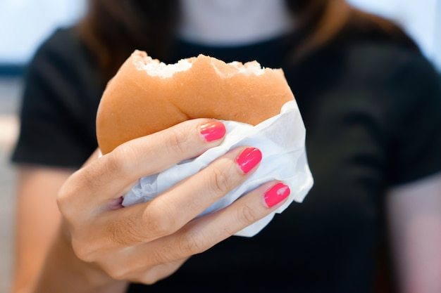Woman hand holding hamburger for fast food