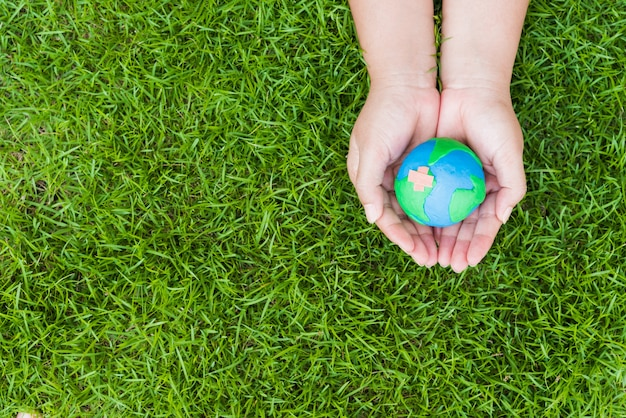 Woman hand holding handmade globe on green grass field background.