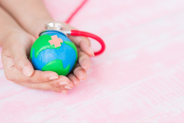 Woman hand holding handmade globe with red stethoscope on pink wooden background