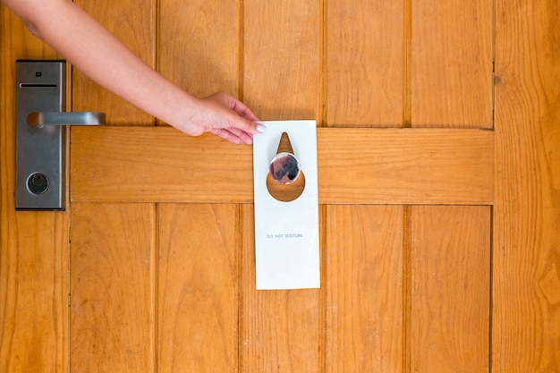 Woman hand holding and hangs signboard do not disturb on the door in hotel