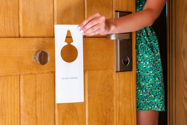 Woman hand holding and hangs signboard do not disturb on the door in hotel Premium Photo