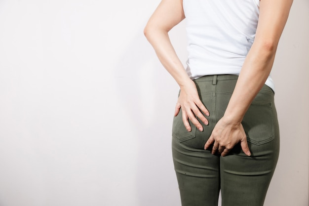 Woman hand holding her bottom.