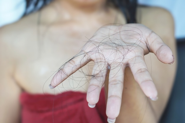 Woman hand holding her hair loss while taking a shower