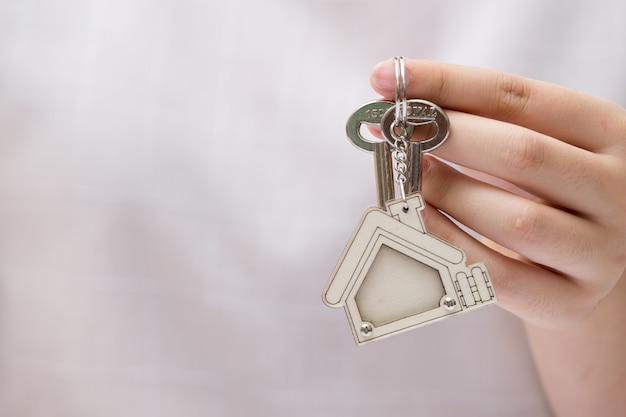 Woman hand holding home key. concept for real estate business.