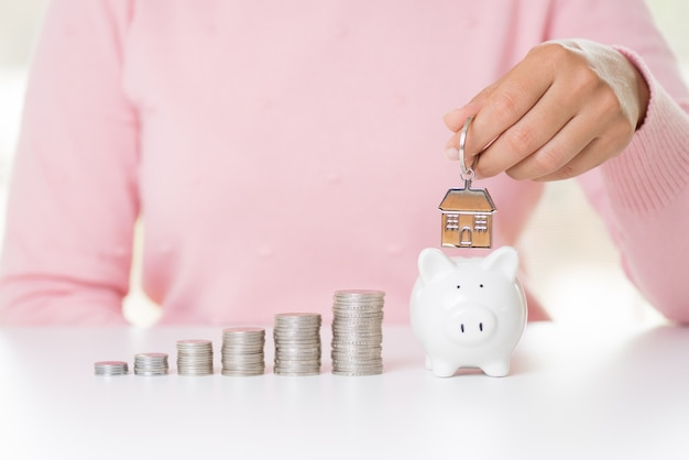 Woman hand holding house keychain with stack of coins and piggy bank