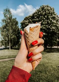夏の晴れた日にアイスクリームを持っている女性の手がクローズアップ。自然な緑の背景。