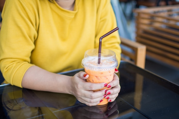 Woman hand holding ice thai tea with straw. soft focus.