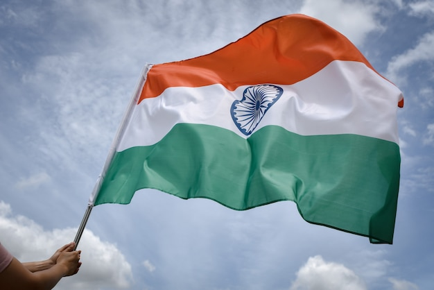 Woman hand holding india flag on the blue sky