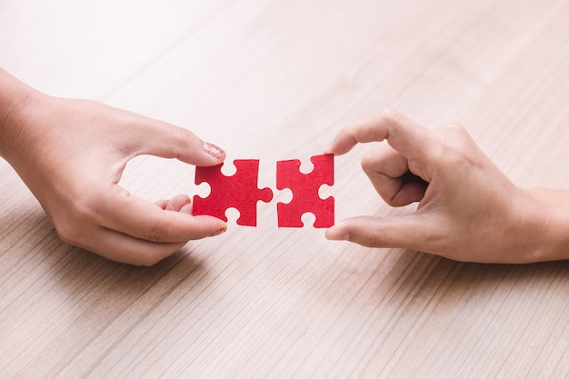Woman hand holding jigsaw puzzle pieces in office