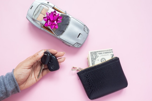 Woman hand holding key with car and money in purse on pink background, flat lay