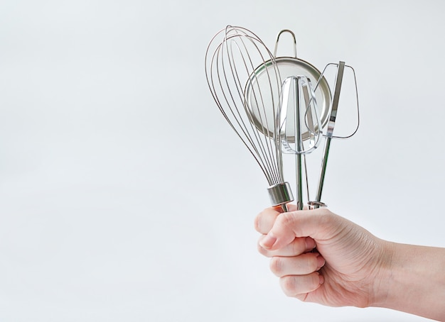Woman hand holding kitchen utensils on grey background with copy space.