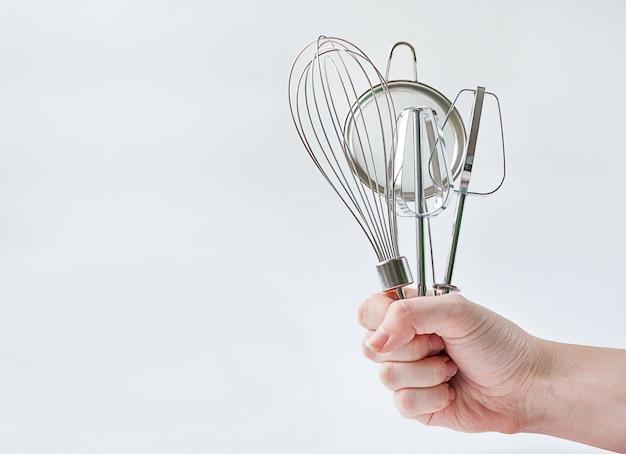 コピースペースと灰色の背景に台所用品を持っている女性の手。