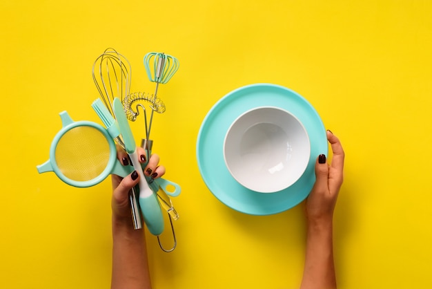 Woman hand holding kitchen utensils on yellow background.