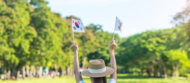 自然の背景に韓国の旗を持っている女性の手。国立財団、開天節、国民の祝日、韓国の光復節、そして幸せなお祝いのコンセプト