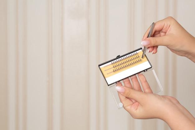 ピンセット付きのケースにまつ毛の束を持っている女性の手。テキスト用のスペース