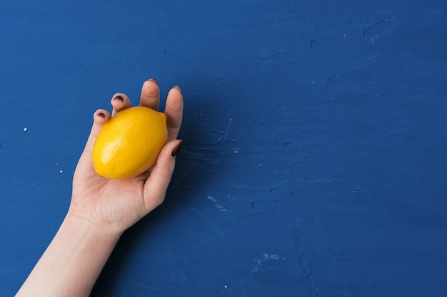 Woman hand holding lemon against classic blue background, top view