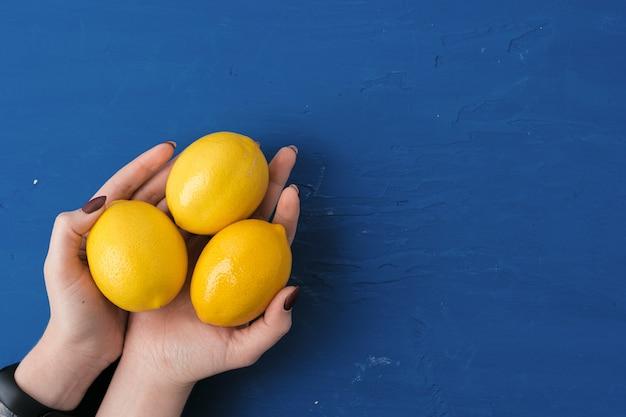 古典的な青いテーブル、上面に対してレモンを持つ女性の手