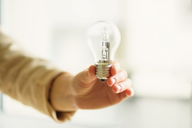 Woman hand holding light bulb on cream background with copy space. creative idea, new business plan, motivation, innovation, inspiration concept.