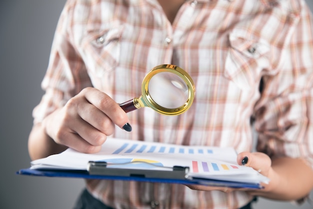 Woman hand holding magnifier with graph
