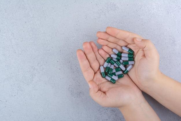 Mano della donna che tiene capsule mediche su marmo.