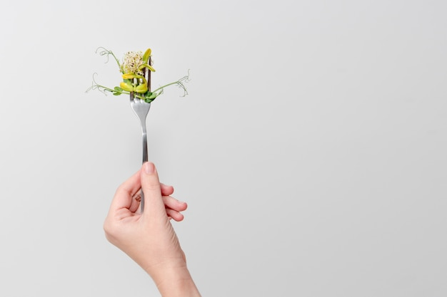 Woman hand holding micro greens on fork.