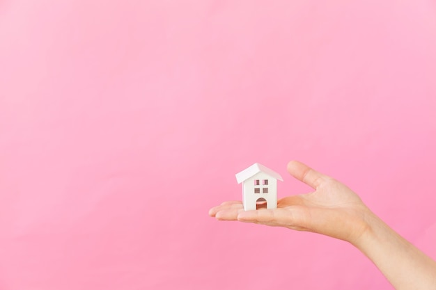 ピンクの背景で隔離のミニチュア白いおもちゃの家を持っている女性の手