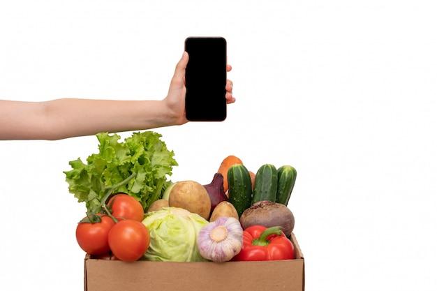 Женщина рука держит мобильный телефон возле овощной коробки