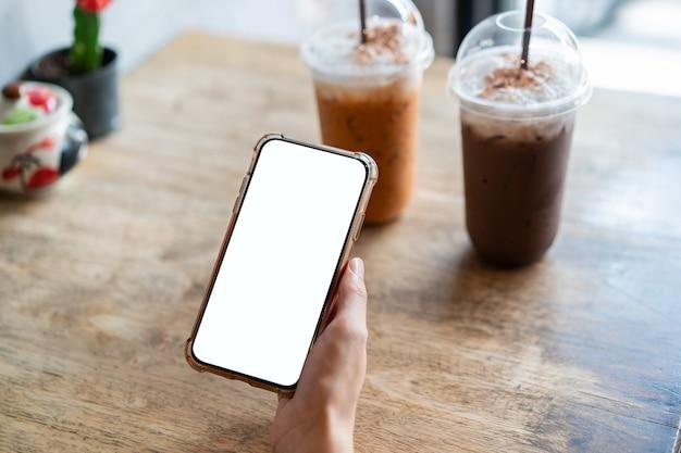 カフェで空白の白い画面で携帯電話を持っている女性の手。