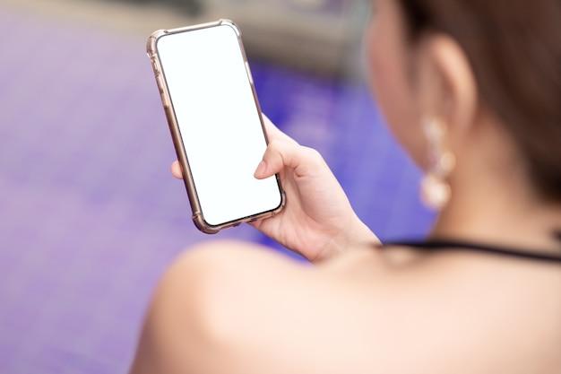 プールサイドの空白の白い画面のモックアップと携帯電話を持っている女性の手。