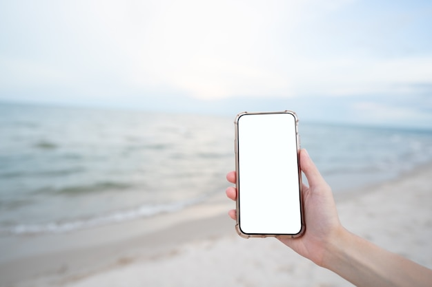 ビーチで空白の白い画面のモックアップと携帯電話を持っている女性の手。