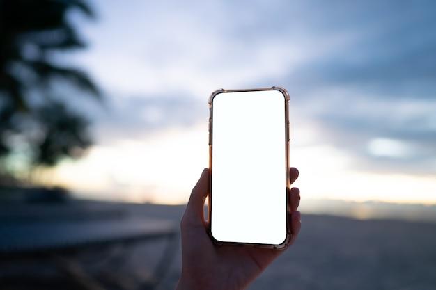朝のビーチで空白の白い画面で携帯電話を持っている女性の手。