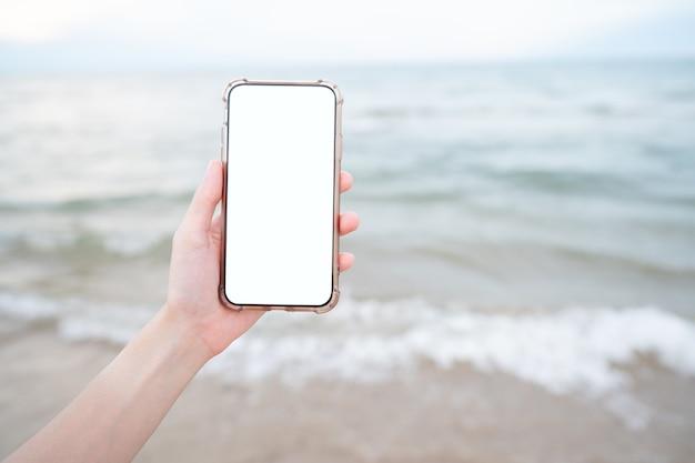 ビーチで空白の白い画面で携帯電話を持っている女性の手。