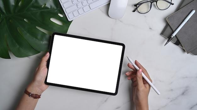 Рука женщины, держащая макет цифрового планшета с пустым экраном и стилусом на мраморном фоне.