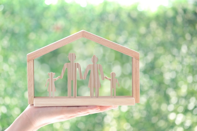 Woman hand holding model house with model family on natural green background