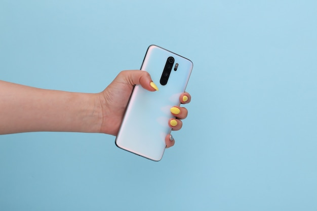 Bliueパステルで現代のスマーフォンを持っている女性の手