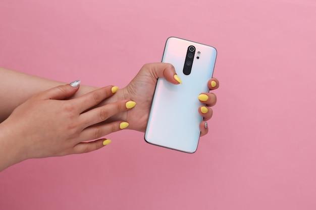 ピンクのパステルカラーでモダンなスマーフォンを持っている女性の手