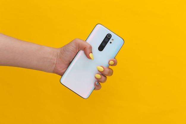 黄色のモダンなスマーフォンを持っている女性の手