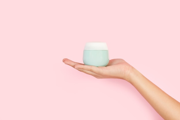 Woman hand holding a moisturizer cream on a pink background with copy space