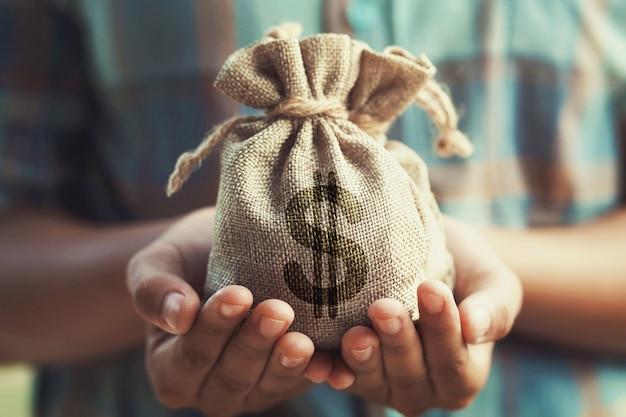여자가 손을 잡고 돈 가방. 개념 절약 금융 및 회계