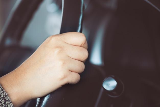 빈티지 컬러 톤의 자동차를 운전하는 동안 검은 스티어링 휠을 잡고 여자 손