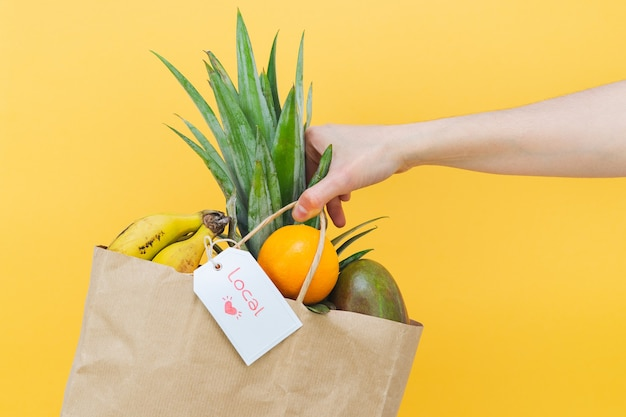 Woman hand holding paper bag full of tropical fruit on yellow background. copy space.