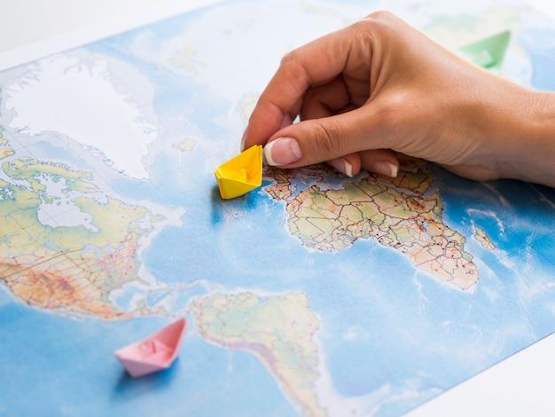Mano della donna che tiene una barchetta di carta su una mappa