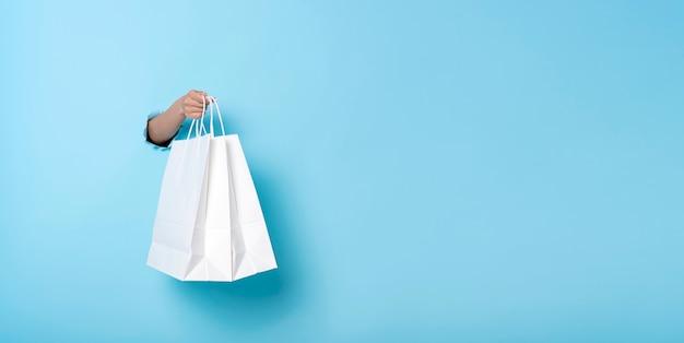 青いバナーの背景に紙の買い物袋を持つ女性の手。割引と販売のコンセプト。パノラマ画像
