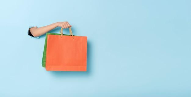 青いバナーの背景に紙の買い物袋を持っている女性の手。割引と販売のコンセプト。パノラマ画像
