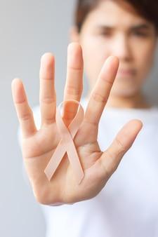 Женщина рука персиковая лента на сентябрь месяц осведомленности рака матки. концепция здравоохранения и всемирного дня рака