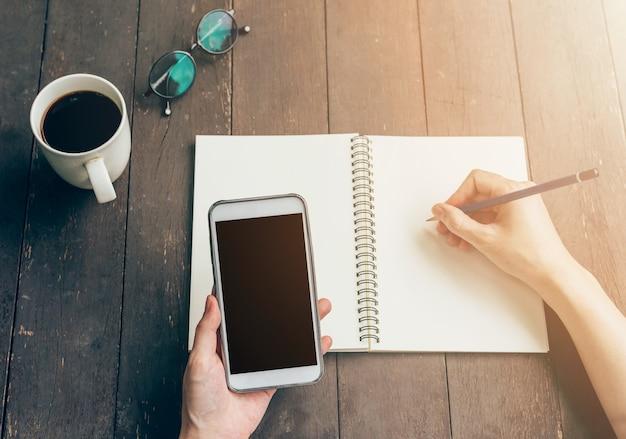 Женщина рука, проведение телефон и руки, писать на столе в саду в кафе с урожай тонированное.
