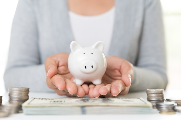Woman hand holding piggy bank with stack of coins and america dollars banknotes