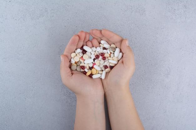 Женщина рука кучу таблеток на мраморе. фото высокого качества