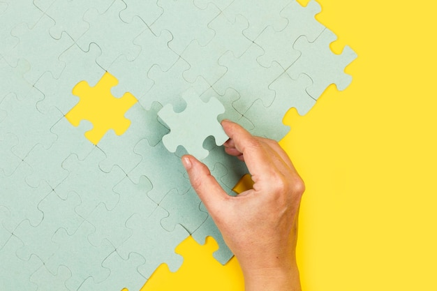 Woman hand holding a pink puzzle piece on a yellow background in a top view