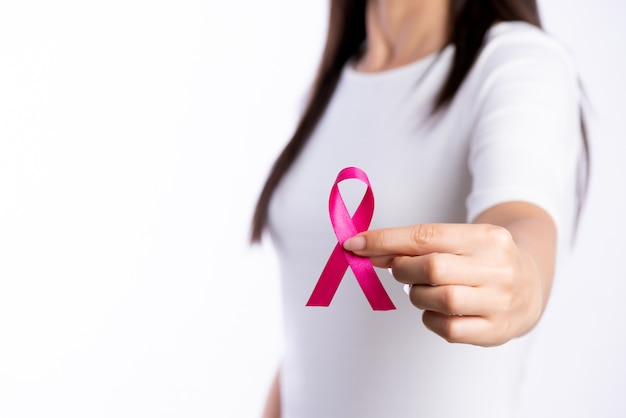 Woman hand holding pink ribbon breast cancer awareness.
